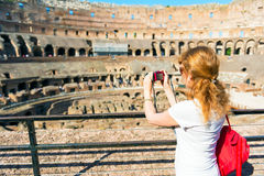 Young female tourist takes a picture inside the Coliseum in Rome stock images