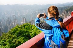 Young female tourist taking photo of mountains in Zhangjiajie. Young female tourist with blue backpack taking photo and enjoying mountain view in the Zhangjiajie stock image