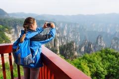 Young female tourist taking photo of Zhangjiajie mountains. Young female tourist with smartphone taking photo and enjoying mountain view in the Zhangjiajie royalty free stock images