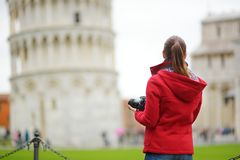 Young female tourist taking photos of the famous Leaning Tower of Pisa. Vacation in Italy, traveling off season royalty free stock photo