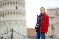 Young female tourist taking photos of the famous Leaning Tower of Pisa. Vacation in Italy, traveling off season royalty free stock image