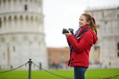 Young female tourist taking photos of the famous Leaning Tower of Pisa. Vacation in Italy, traveling off season stock photos