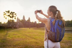 Young female tourist taking picture of Angkor Wat in Cambodia Royalty Free Stock Photography