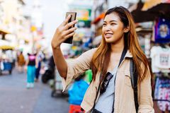 Young female tourist taking selfie photos with smartphone in Thailand. Young Asian female tourist woman taking selfie photos with smartphone while travelling in stock images