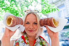 Young female tourist with traditional czech dessert called trdelnik. Prague Royalty Free Stock Image