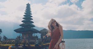 Young female tourist at Ulun Danu Batur temple in Indonesia, on the island of Bali. Spiritual and well-known place. Lifestyle, tra Stock Images