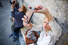 Young female tourist using her smart phone to capture photos. From her summer vacation trip in an old italian city she is disovering shallow DOF; color toned Stock Photos