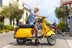 Young Female tourist wearing backpack bag parking traditional italian yellow vintage urban retro scooter on the street. Young casual blond woman wearing backpack stock images