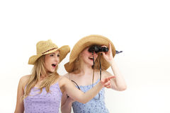 Young female tourists with binocluars. Two attractive young female tourists in sunhats with binocluars looking into the distance while exclaming and pointing in Stock Image