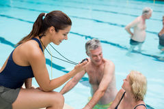 Young female trainer monitoring time of senior swimmers at poolside. Side view of young female trainer monitoring time of senior swimmers at poolside Stock Image