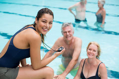 Young female trainer and senior swimmers at poolside. Portrait of young female trainer and senior swimmers at poolside Royalty Free Stock Photo
