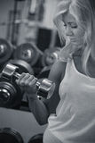 Young female training biceps in gym. Young female training biceps with dumbbell in the gym. Monochrome stock photos