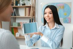Young female travel agent consultant in tour agency with a customer showing online service. Young women travel agent in tour agency working with a client showing Stock Photography