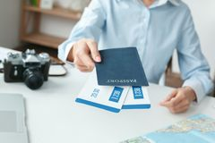 Young female travel agent consultant in tour agency documents close-up. Young woman travel agent in tour agency sitting giving passports and tickets close-up Royalty Free Stock Photos