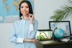 Young female travel agent consultant in tour agency headset communication. Young woman travel agent in tour agency standing wearing headset holding microphone Royalty Free Stock Image