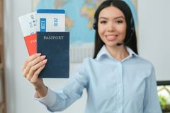 Young female travel agent consultant in tour agency holding documents. Young woman travel agent in tour agency standing wearing headset holding passports and Royalty Free Stock Photo