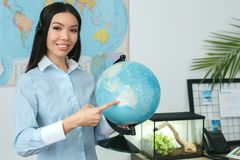 Young female travel agent consultant in tour agency holding globe. Young woman travel agent in tour agency pointing destination on a globe smiling friendly Stock Photography