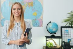Young female travel agent consultant in tour agency holding magazine. Young woman travel agent in tour agency holding magazinr smiling Stock Photography
