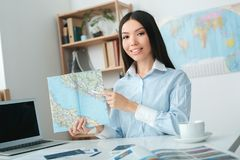 Young female travel agent consultant in tour agency holding map. Young woman travel agent in tour agency sitting holding map looking camera smiling Stock Image