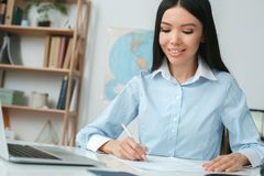Young female travel agent consultant in tour agency planning. Young woman travel agent in tour agency sitting working writing documents concentrated smiling Royalty Free Stock Photography