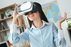 Young female travel agent consultant in tour agency playing virtual reality headset royalty free stock images