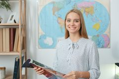 Young female travel agent consultant in tour agency reading magazine royalty free stock photos