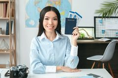 Young female travel agent consultant in tour agency showing documents. Young woman travel agent in tour agency sitting showing passports and tickets smiling Royalty Free Stock Photos