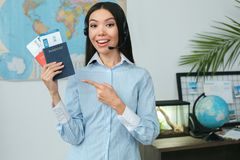Young female travel agent consultant in tour agency showing documents. Young woman travel agent in tour agency standing wearing headset showing passports and Royalty Free Stock Photo
