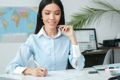 Young female travel agent consultant in tour agency writing and communicate using headset. Young woman travel agent in tour agency sitting writing documents and Royalty Free Stock Photography