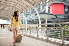 Young Female traveler in Bangkok city. Asian beauty young Female traveler walking and pulling luggage in modern city with sky with urban Bangkok architecture Stock Photo