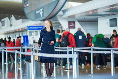 Young female traveler in international airport. Young woman in international airport, walking with her luggage Stock Photos