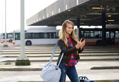 Young female traveler looking at mobile phone Royalty Free Stock Images