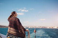 Woman enjoing beautiful Bosphorus view and traveling to Istanbul. Young female traveler sailing on a ferry to Bosporus strait in Istanbul and enjoying simple Royalty Free Stock Photography