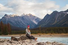 Young female traveller poses on the river stones with a breathtaking background behind, Travel Alberta, Canada, Canadian Rockies royalty free stock photo