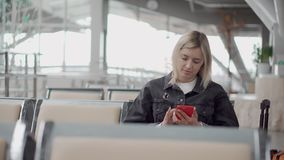 Blonde girl with smartphone in airport. stock video