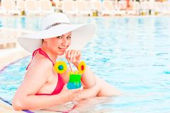 Young female trying to drink in a glass in the pool Royalty Free Stock Photo
