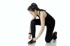 Young female tying her shoelaces. Young female wearing sportswear, tying her shoelaces with isolated on white background royalty free stock photo