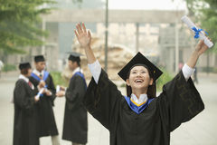 Young Female University Graduate, Arms Raised in the Air with Diploma Royalty Free Stock Photos
