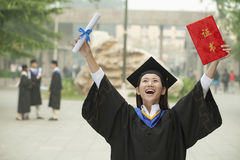 Young Female University Graduate, Arms Raised in the Air with Diploma Royalty Free Stock Images