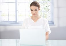 Young female using laptop at home Stock Image