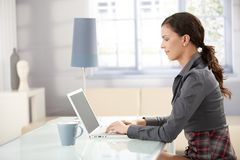 Young female using laptop at home smiling. Young female working at home, using laptop, smiling stock photo