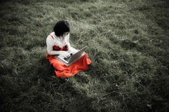 Young female using a laptop in nature Stock Image