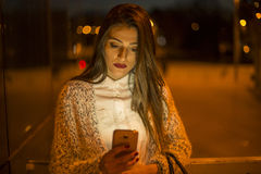 Young female using mobile phone outdoor in the night Stock Images