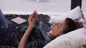 Young female using smartphone on bed by window stock footage