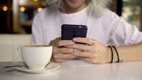 Female using smartphone while drinking coffee. Young female using smartphone while drinking coffee stock video footage
