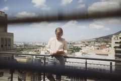 Young female using tablet PC on a balcony stock image