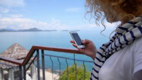 Young Female Using a Touchscreen Smartphone. Young woman using a touchscreen smartphone against the sea view.. HD, 1920x1080 stock video footage