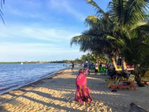 A young female vacationer goes for a peaceful stroll along the sandy beaches of beautiful Placencia, Belize stock photo