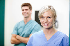 Young Female Vet In Scrubs Smiling. Portrait of young female vet in scrubs smiling with colleague standing in background Royalty Free Stock Photos