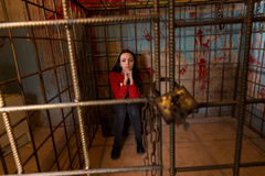 Young female victim imprisoned in a metal cage with a blood spla. Ttered wall behind her sitting in terror awaiting a fate Royalty Free Stock Photos